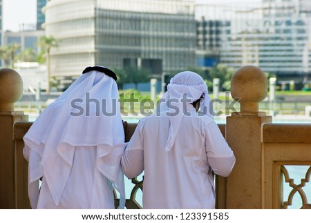 Two anonymous Arab men in traditional white clothing - stock photo
