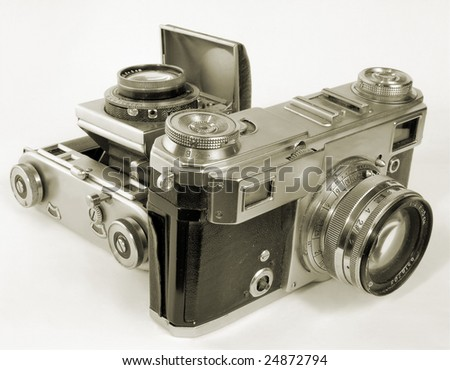 Two antiquarian 35-mm film cameras with put-forward lens. - stock photo