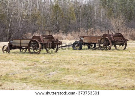Two antique manure spreaders in a rural farm field.