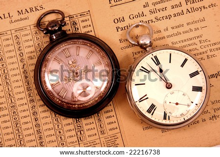 Two antique pocket watches on antique hall mark guide. - stock photo