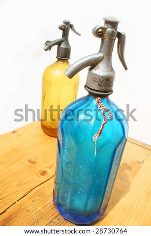 Two antique seltzer bottles on weathered wooden table and white background - stock photo