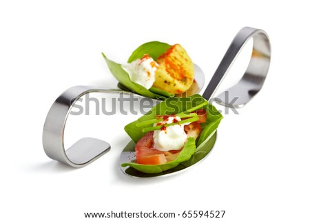 Two appetizer spoons garnished with basil tomato, potato and curd