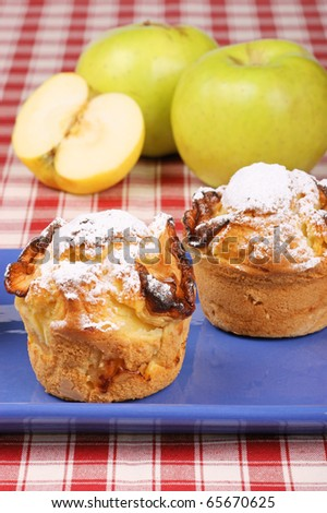 Two apple muffins on a blue plate with apples in the background. Studio shot. Selective focus, shallow DOF. - stock photo