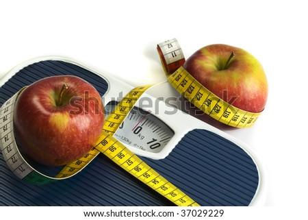 two apples and a tape measure on bathroom scales