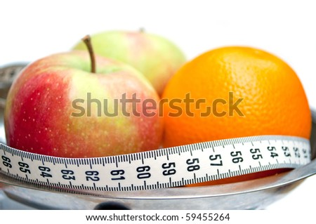 Two apples and orange wrapped with centimeter tape (centimeter tape show number 60, ideal for waist) - stock photo