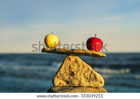 Two apples in balance on the top of stone - stock photo