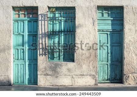 Two aqua green painted wooden doors and window of rustic exterior of old colonial style building illuminated by morning light in Merida, Yucatan, Mexico - stock photo