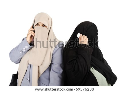 Two  Arab woman speaking on phone - stock photo