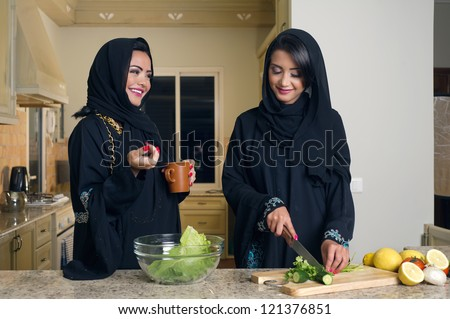 Two Arabian Women gathering cooking & drinking coffee in kitchen - stock photo