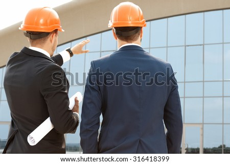 Two architect assessing their building progress outdoors - stock photo