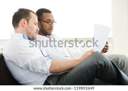 Two architects at work discussing a project - stock photo