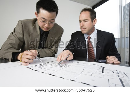 Two architects discussing on blueprints in an office. - stock photo