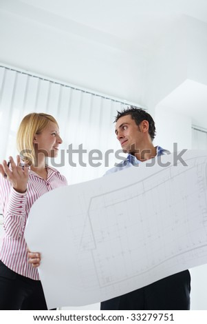 two architects examining blueprint indoors. Copy space - stock photo