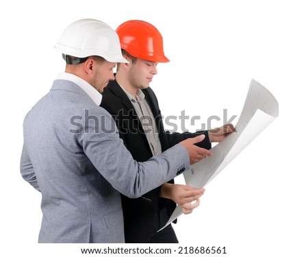 Two architects in hard hats and suits standing discussing a building plan that they are holding open in their hands, side view on white - stock photo