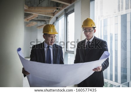 Two architects in hardhats examining blueprint in office building - stock photo