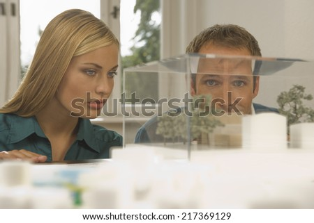 Two architects looking at an architectural model - stock photo