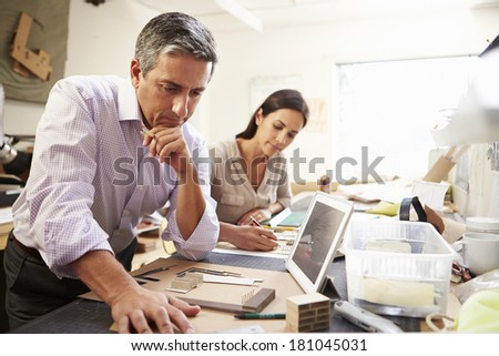 Two Architects Making Models In Office Using Digital Tablet - stock photo