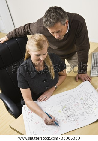 Two architects, male standing over female, looking at the drawing on the desk. Vertical - stock photo