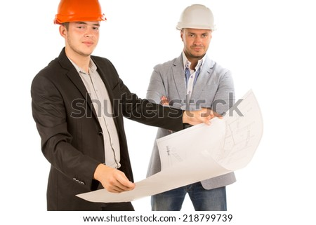 Two architects or structural engineers standing looking at a building plan or blueprint which one of them is holding watched by his confident older partner, on white