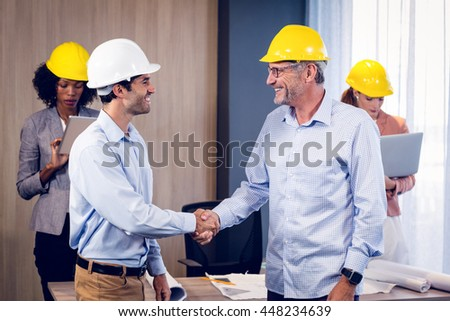 Two architects shaking hands after a meeting in office and colleagues working in background