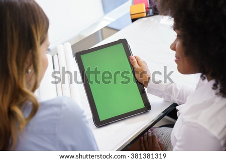Two architects sitting on desk with blueprints and housing projects. The women hold a tablet and surf the web. The display has a green screen - stock photo