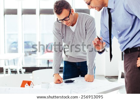 Two architects standing at a desk and discussing a project - stock photo