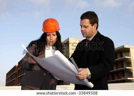 Two architects standing in front of a building site checking project.