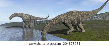 Two argentinosaurus dinosaurs drinking next to water in green landscape by day