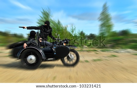 Two armed men riding a motorcycle with a sidecar. Motion blur. - stock photo