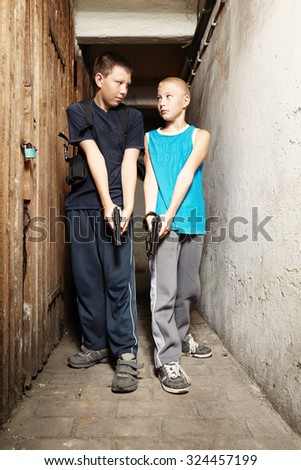 Two armed teenagers in basement - stock photo