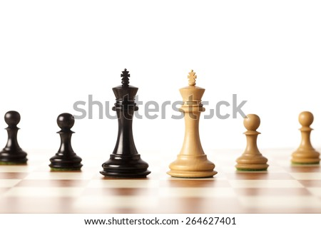 Two armies - black and white chess kings with pawns standing on a chessboard - closeup - stock photo