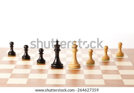 Two armies - black and white chess kings with pawns standing on a chessboard in perspective - stock photo