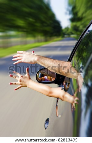 Two arms sticking out of the car - stock photo