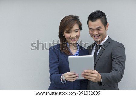 Two Asian Business colleagues standing using digital tablet computer, leaning against a grey wall. Chinese Business team meeting with a tablet PC.