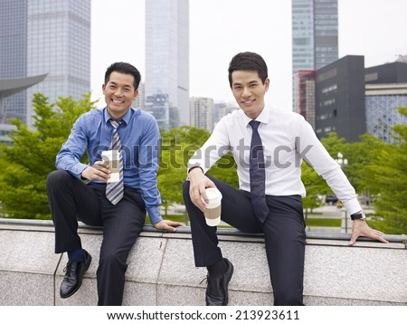two asian business executives talking in city park while taking a coffee break. - stock photo