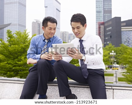 two asian business executives using ipad in city park. - stock photo