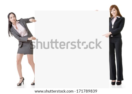 Two Asian business women introduce and hold a blank board, full length portrait isolated on white background.