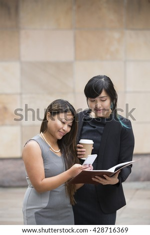 Two Asian Business women using a Smart phone, outside there office building. - stock photo