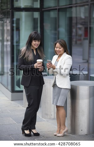 Two Asian Business women using a Smartphone, outside there office building. - stock photo
