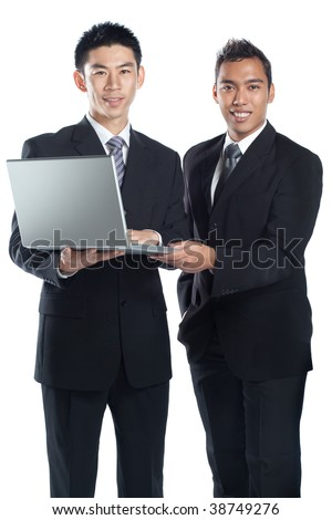 Two Asian businessmen, Chinese and Malay, holding a laptop together signifying racial harmony and international, regional cooperation in Asia.  Both wearing suit, tie, shirt, formal wear. - stock photo