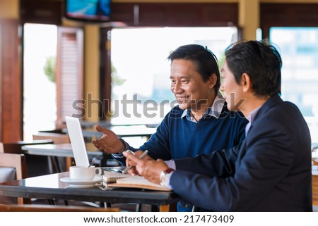 Two Asian businessmen having meeting in the cafe - stock photo