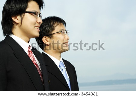 Two asian businessmen posing outdoor at the beach - stock photo