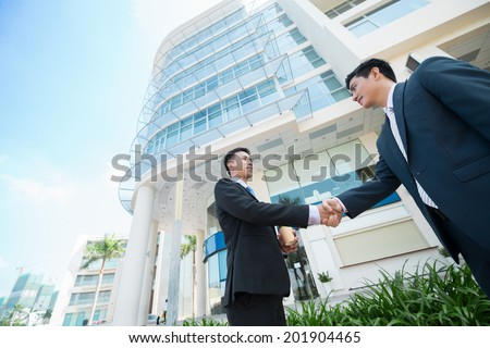 Two Asian businessmen shaking their hands, view from below