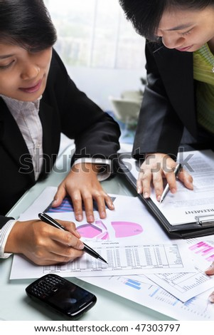 Two Asian businesswoman working together in office - stock photo