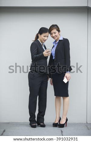 Two Asian Businesswomen using Smartphone, leaning against a grey wall. - stock photo