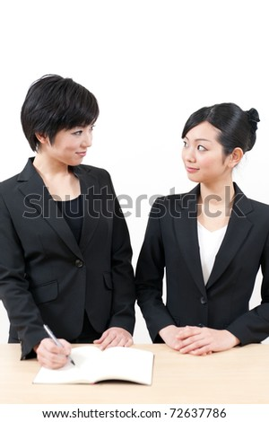 two asian businesswomen working on the table