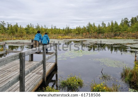 Two Asian Children learning about nature by observing wildlife in a swamp area - stock photo