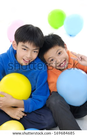 Two asian children with colorful balloons  - stock photo
