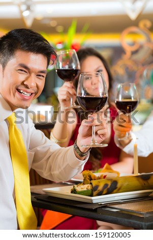 Two Asian Chinese Couples or friends or business people toasting during dinner or lunch in a elegant restaurant with red wine glasses - stock photo