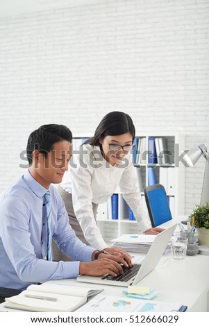 Two Asian colleagues working on report together